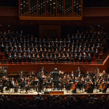 Orchestra and large choir performing on stage with pipe organ above choir.