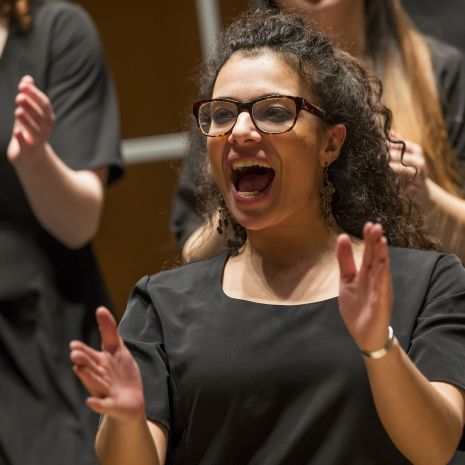 Student with curly hair and glasses singing and clapping hands