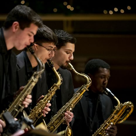Four saxophonists performing in section