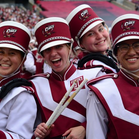 Four smiling marching band members in cherry and white uniforms