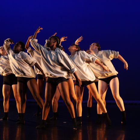 Seven dancers all leaning to one side with same arm in curved upward