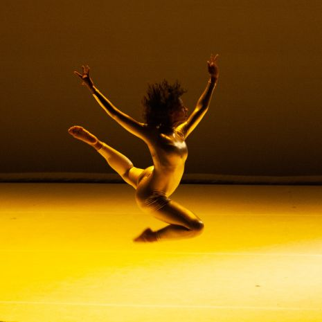 Dancer onstage jumping in air with arms above their head