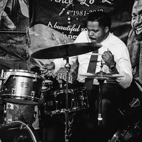 Black and white image of Justin Faulkner at a drum set