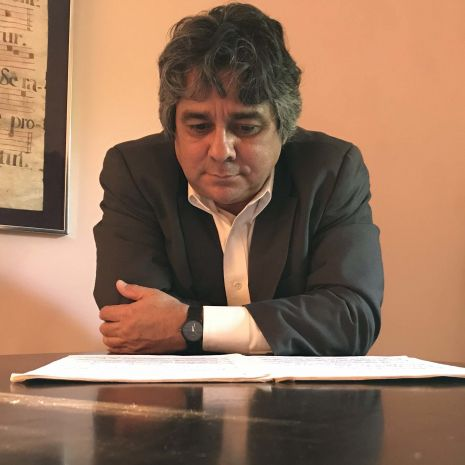 Dr. Emiliano Pardo Tristan is leaning on a piano and reading a score
