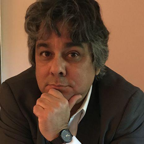 A headshot of Dr. Emiliano Pardo-Tristán on a salmon-pink background