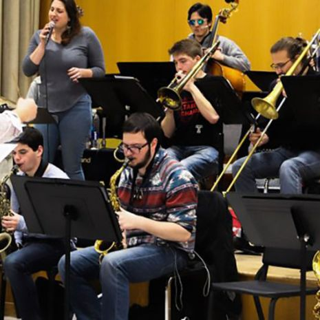 Multiple musicians rehearsing together with a conductor