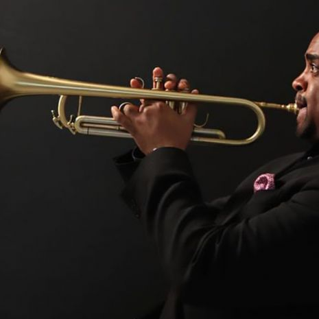 Terell Stafford playing the trumpet on a dark background