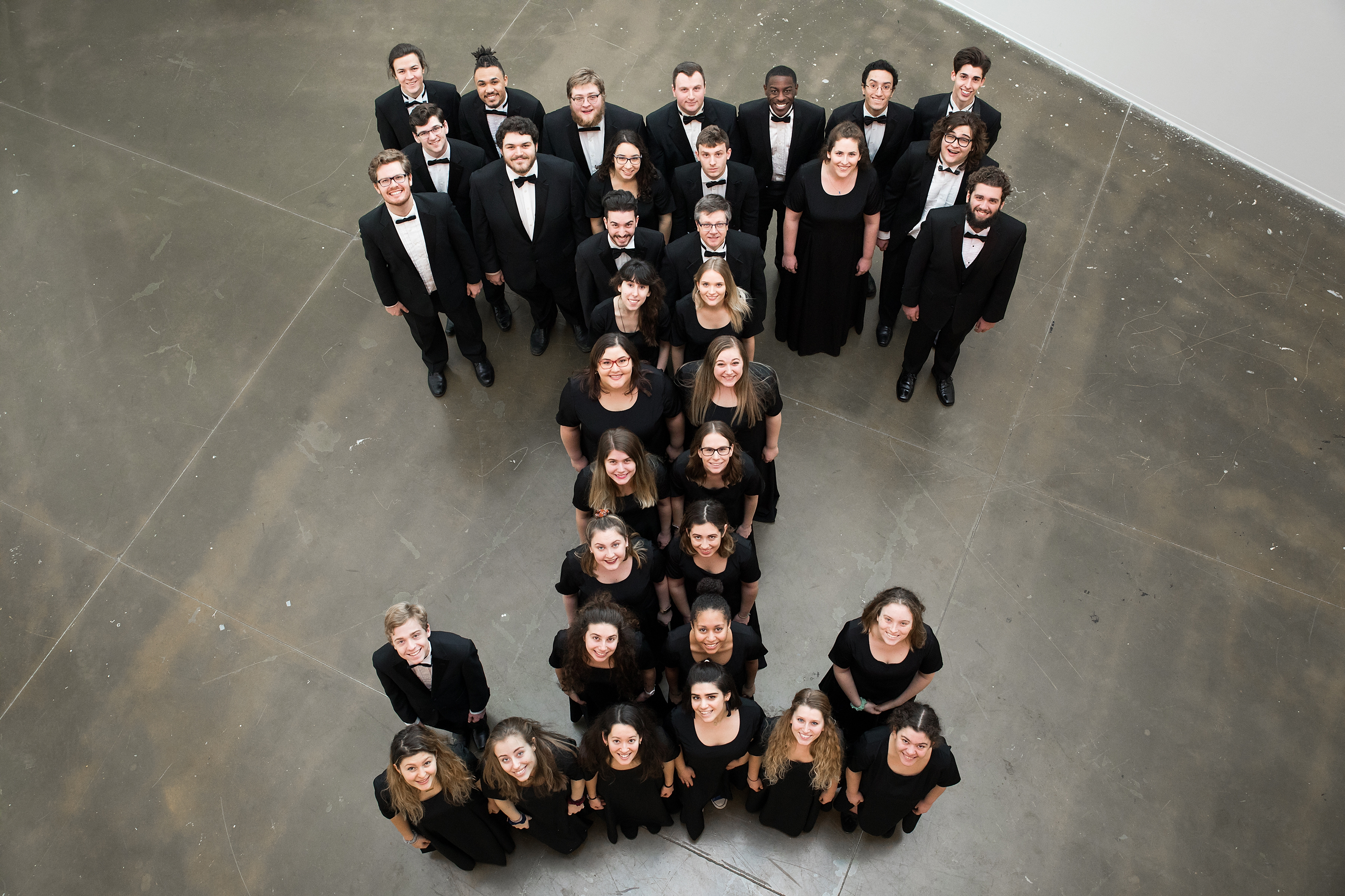 """Image of students in concert dress looking up and standing in a """"T"""" formation"""