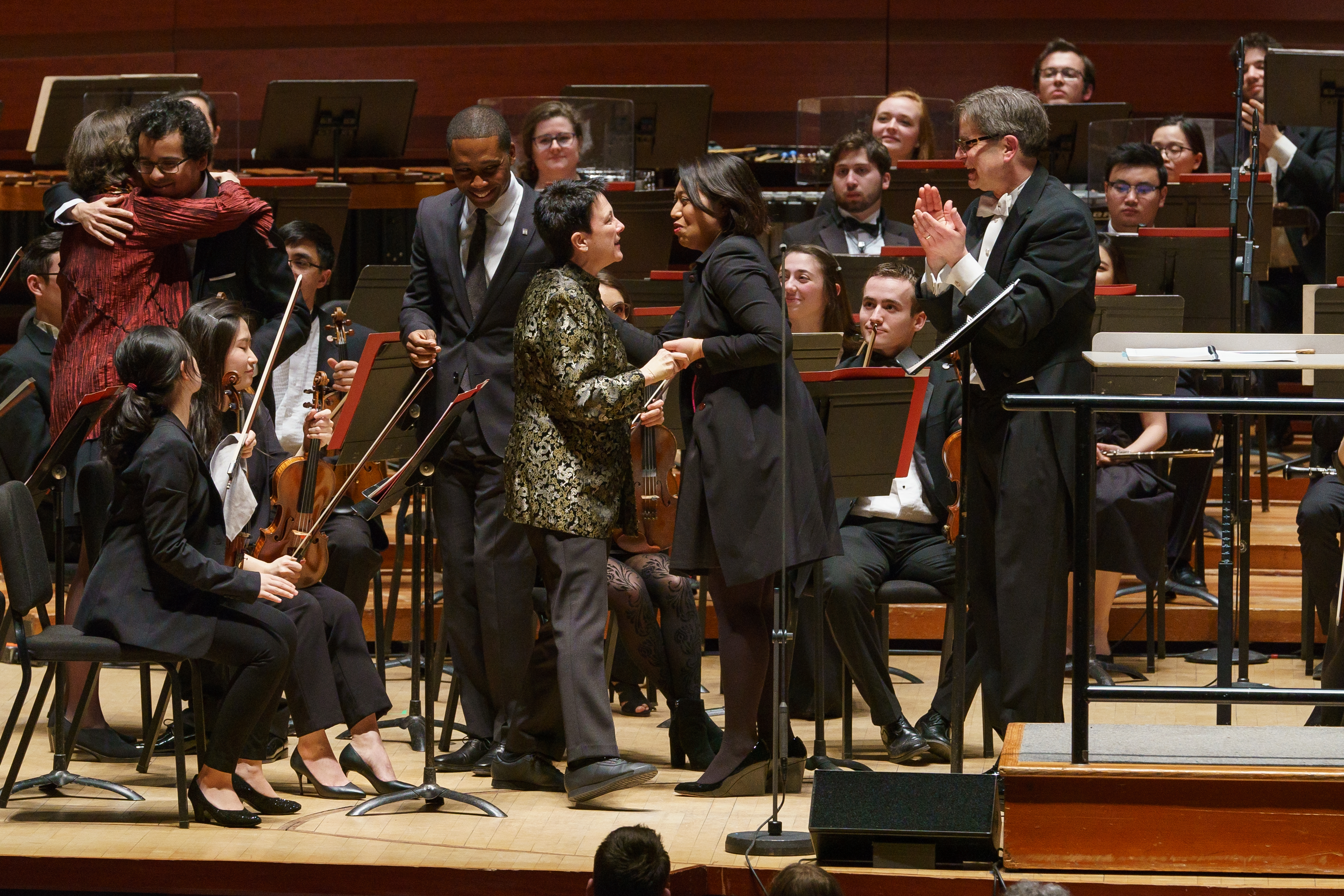 composer greets conductor on stage