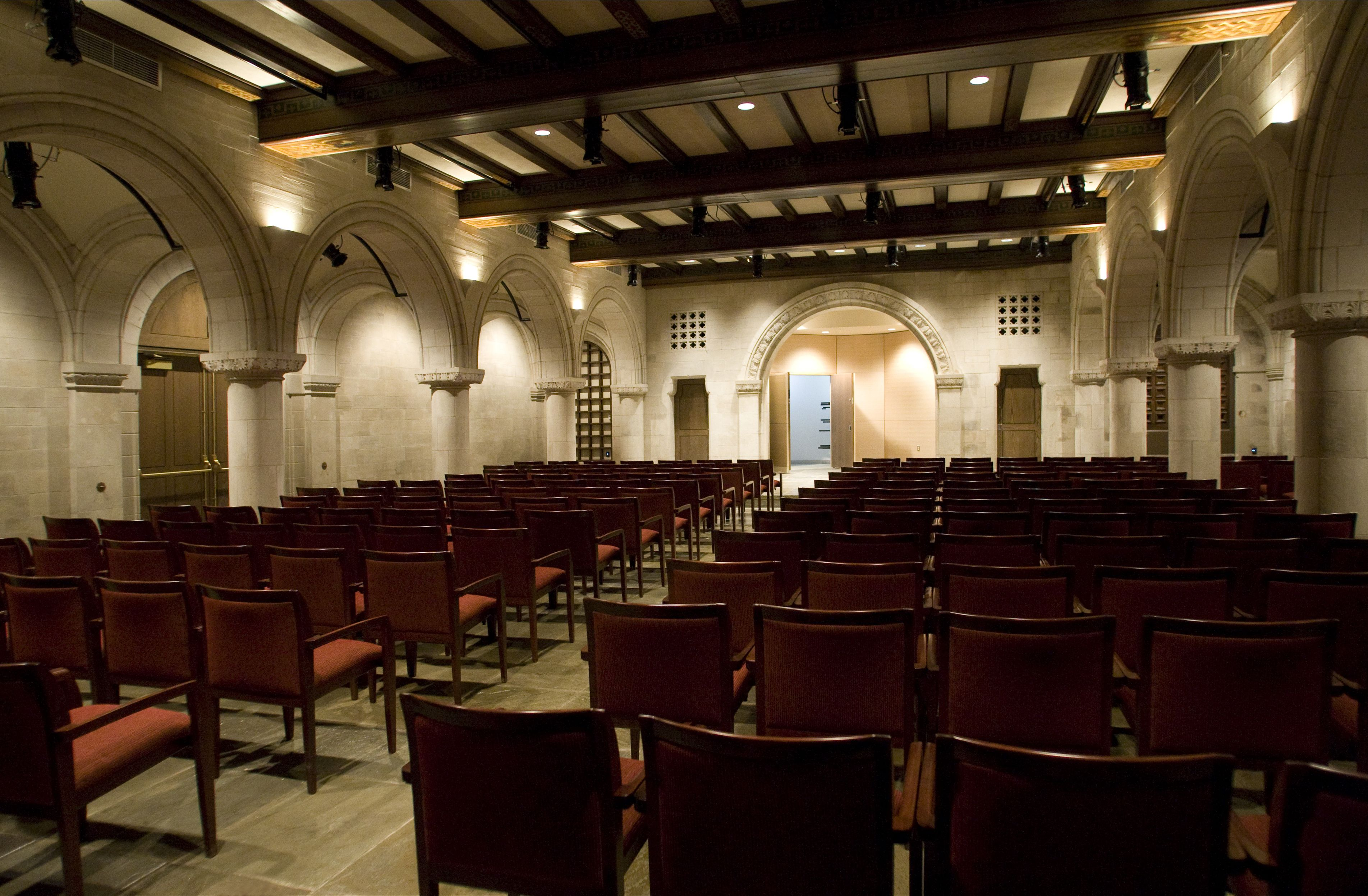 Red upholstered audience chairs set up in stone chapel with arches and small stage