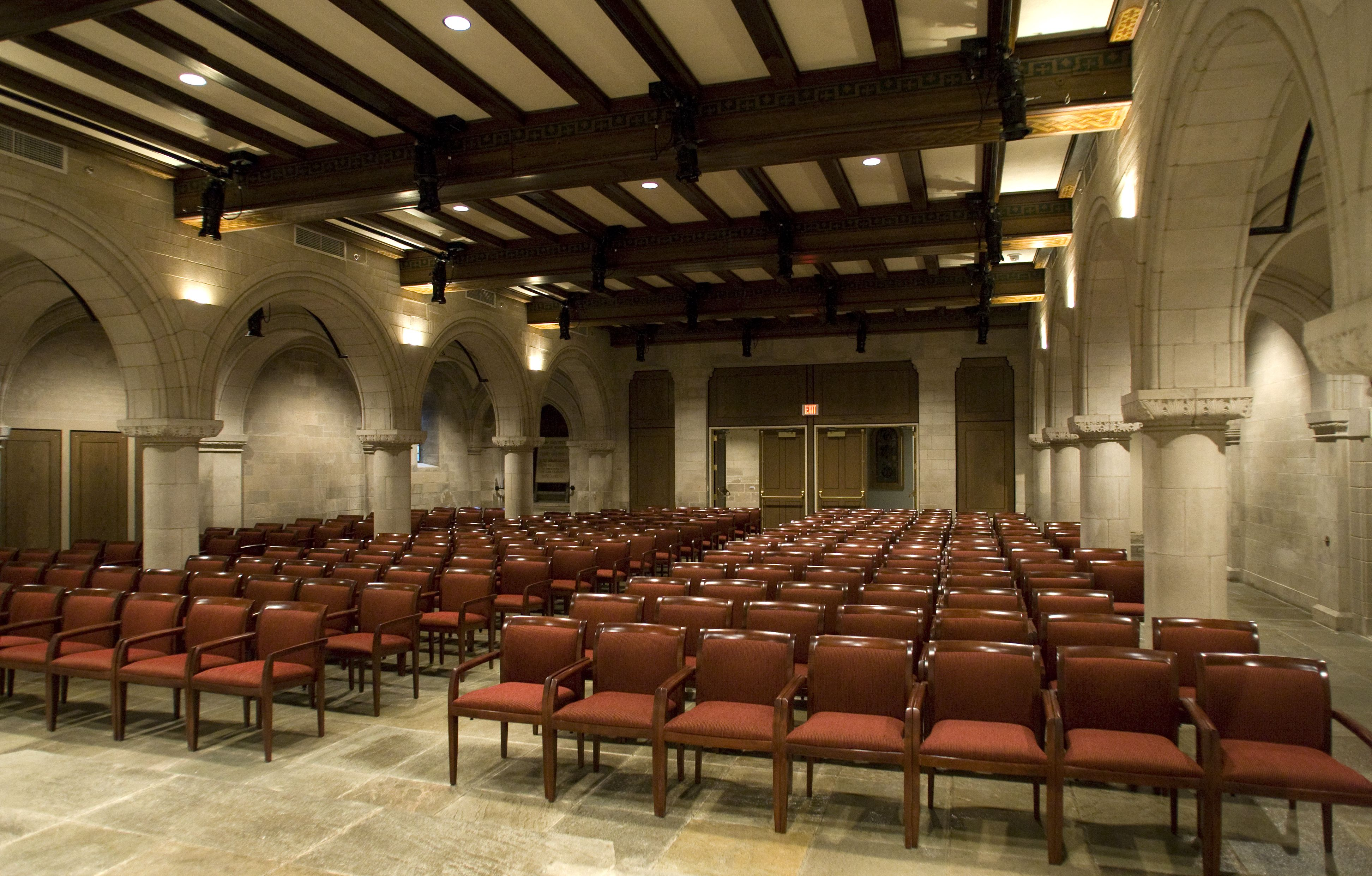 Rows of red upholstered armchairs for audience