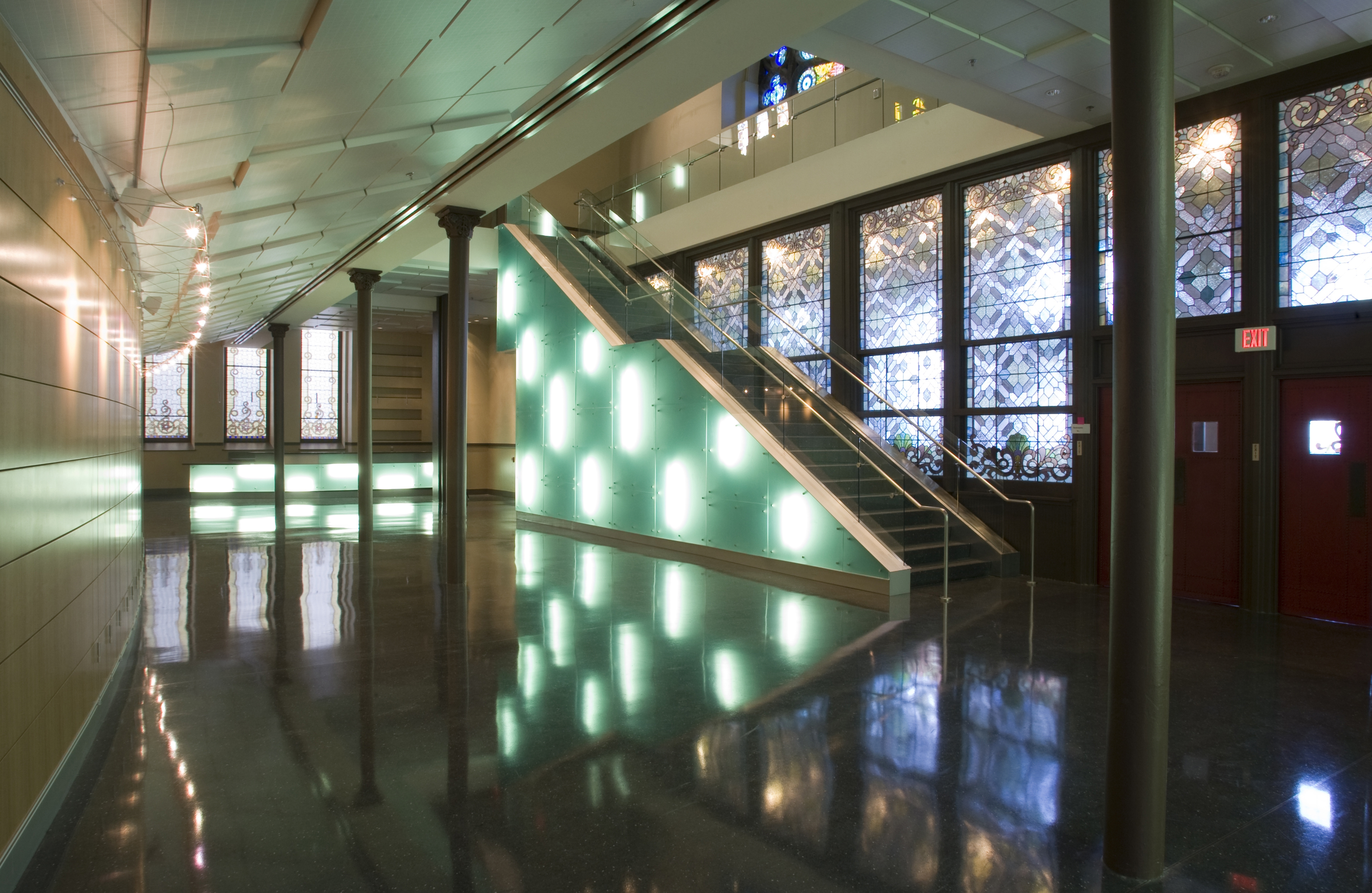 Performance hall lobby with illuminated staircase and stained glass windows