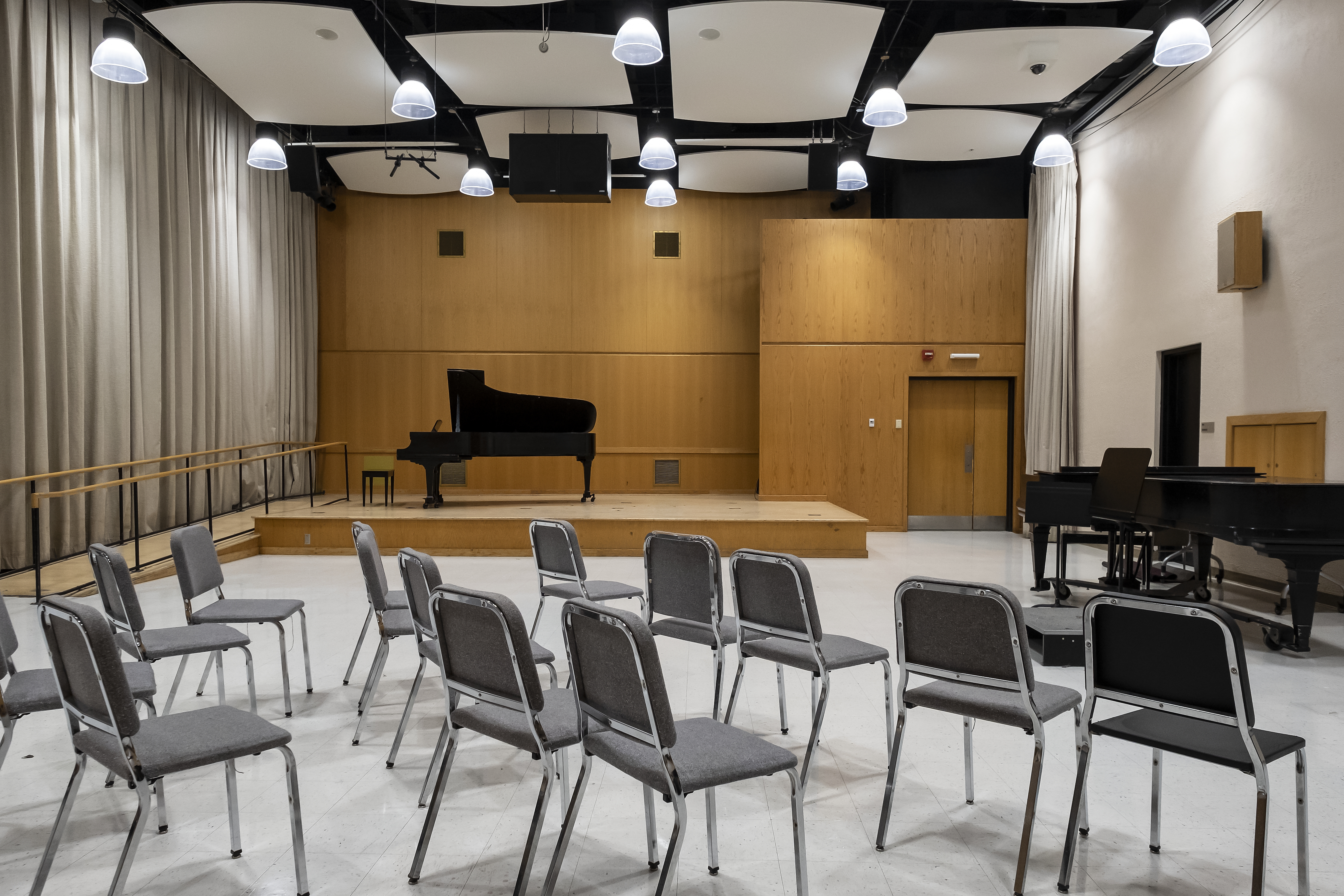 Rehearsal room with two grand pianos, gray chairs set in three rows
