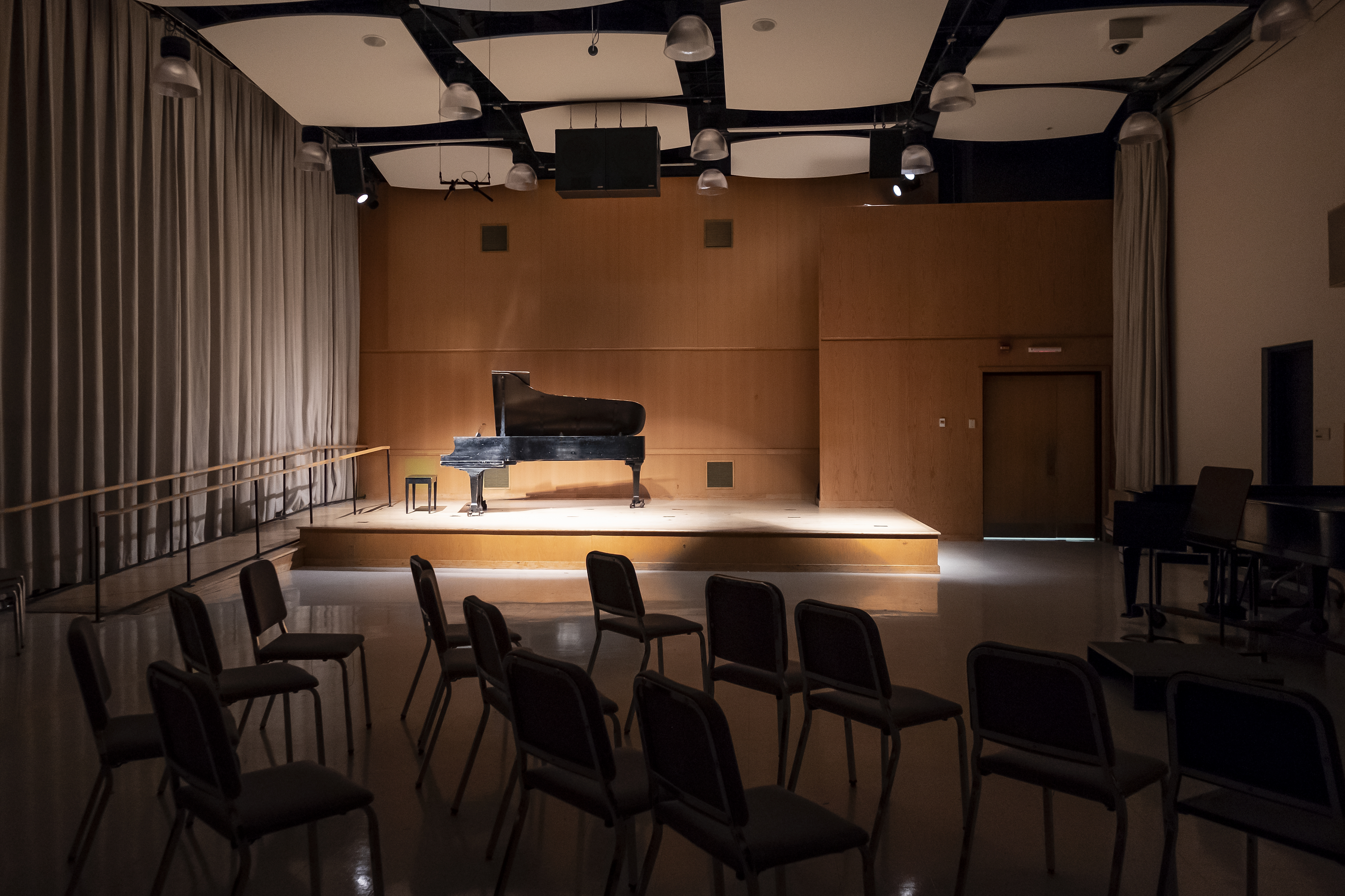 Wooden stage with grand piano on it, audience lights are dimmed and spotlight on piano