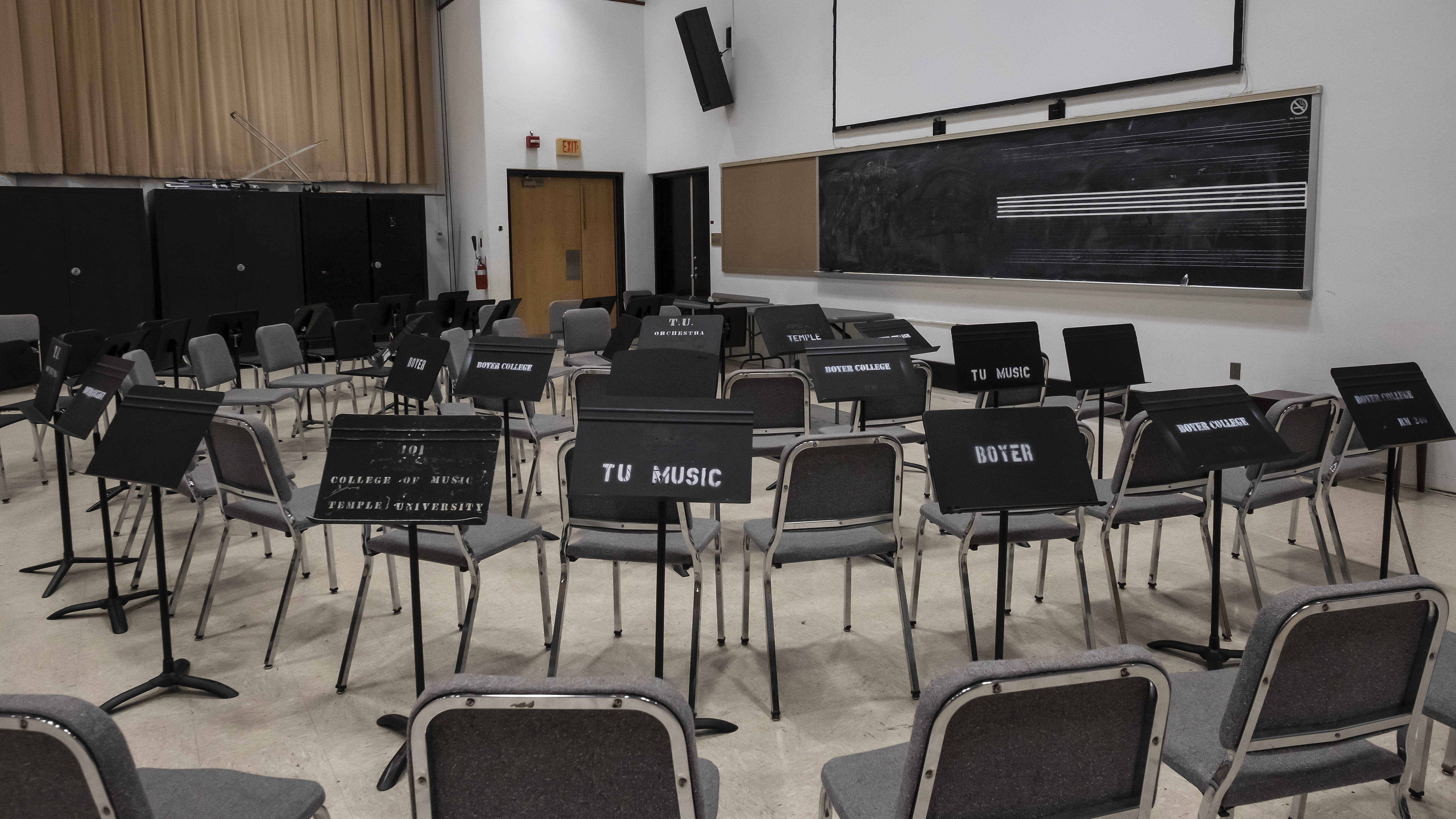 Three rows of chairs in a semicircle, facing podium and chalkboard