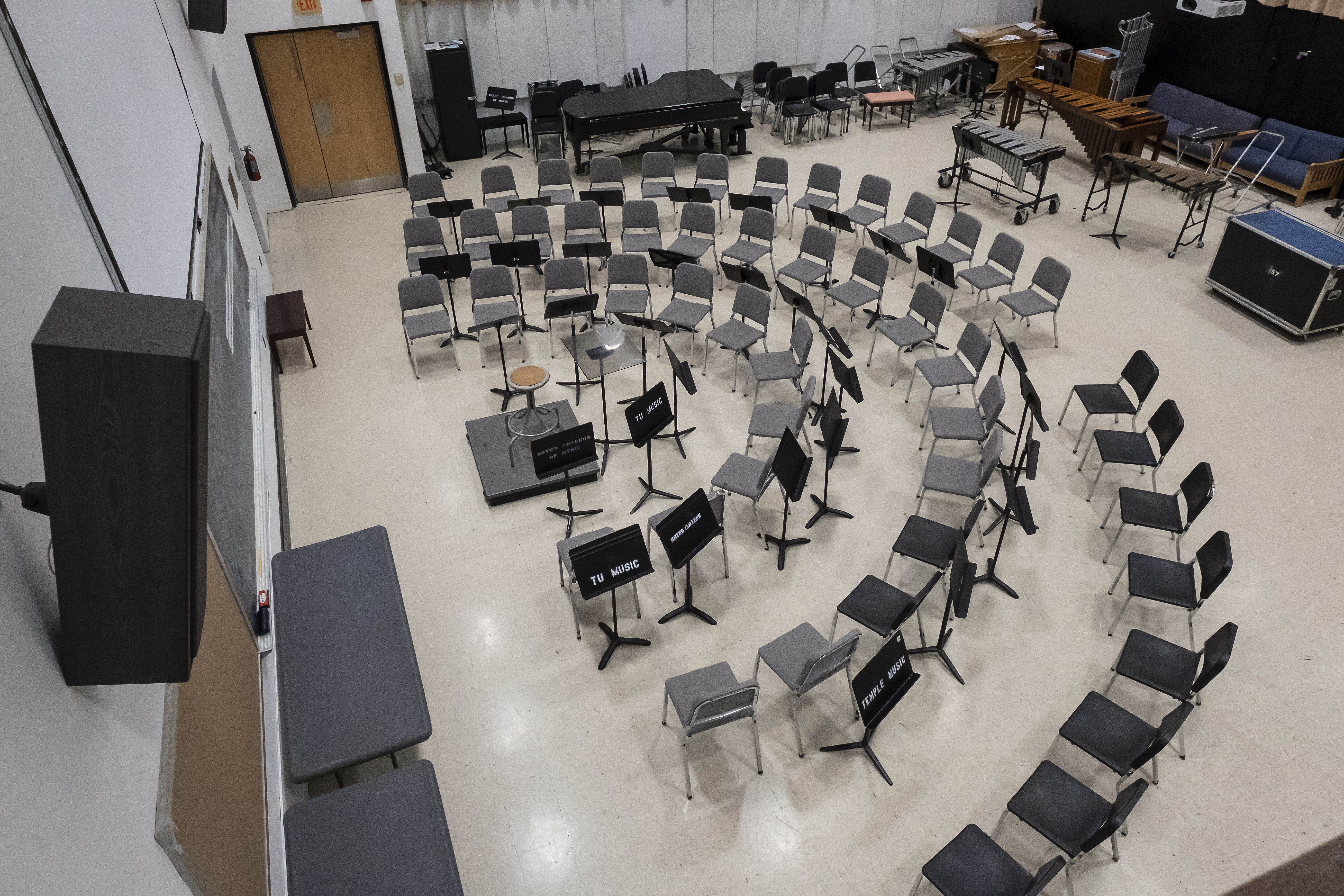 Aerial photo of large rehearsal room, conductor's podium with three rows of seats in a semicircle around it