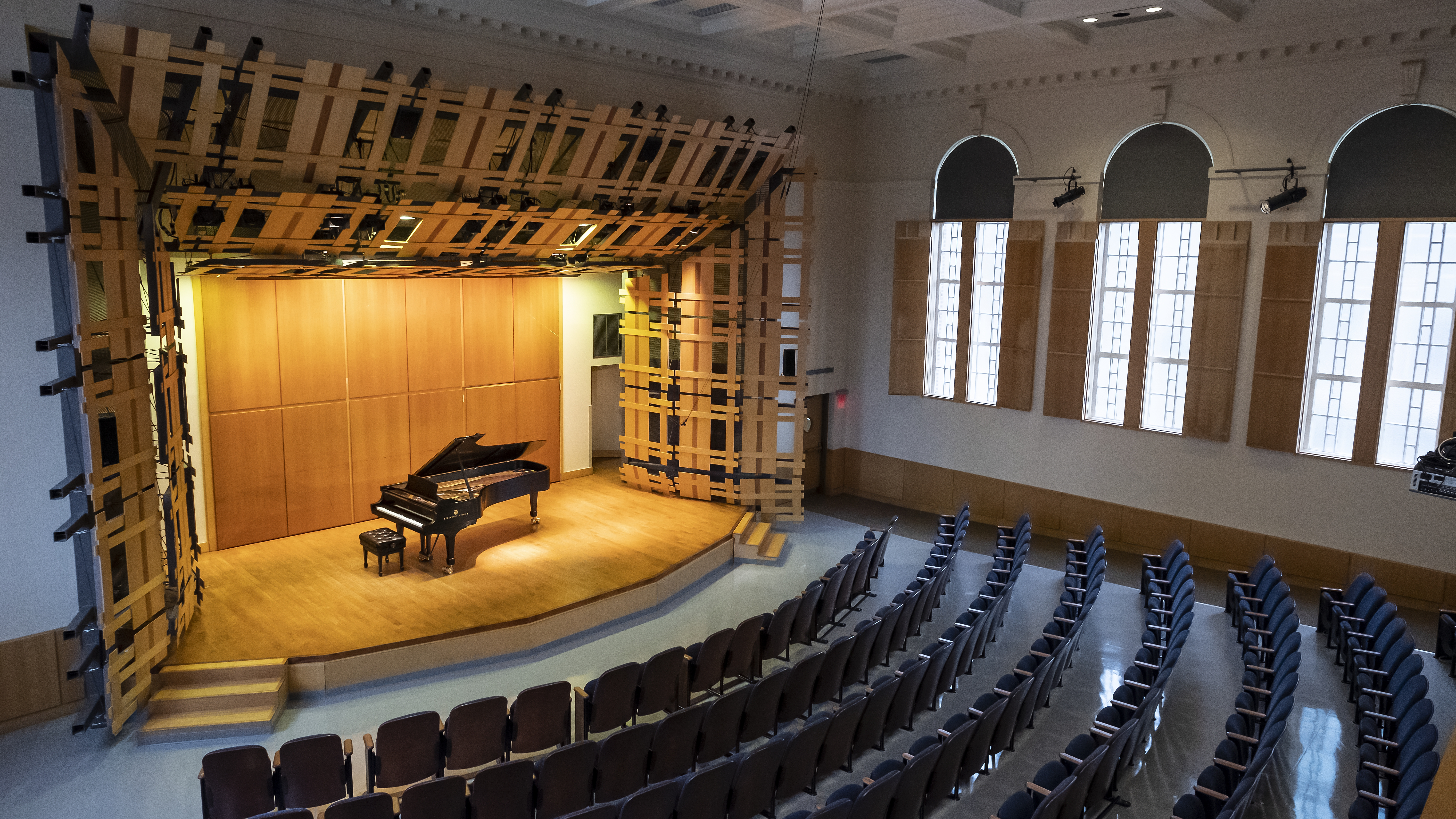 Photo of auditorium, seating and stage with grand piano, from corner balcony view