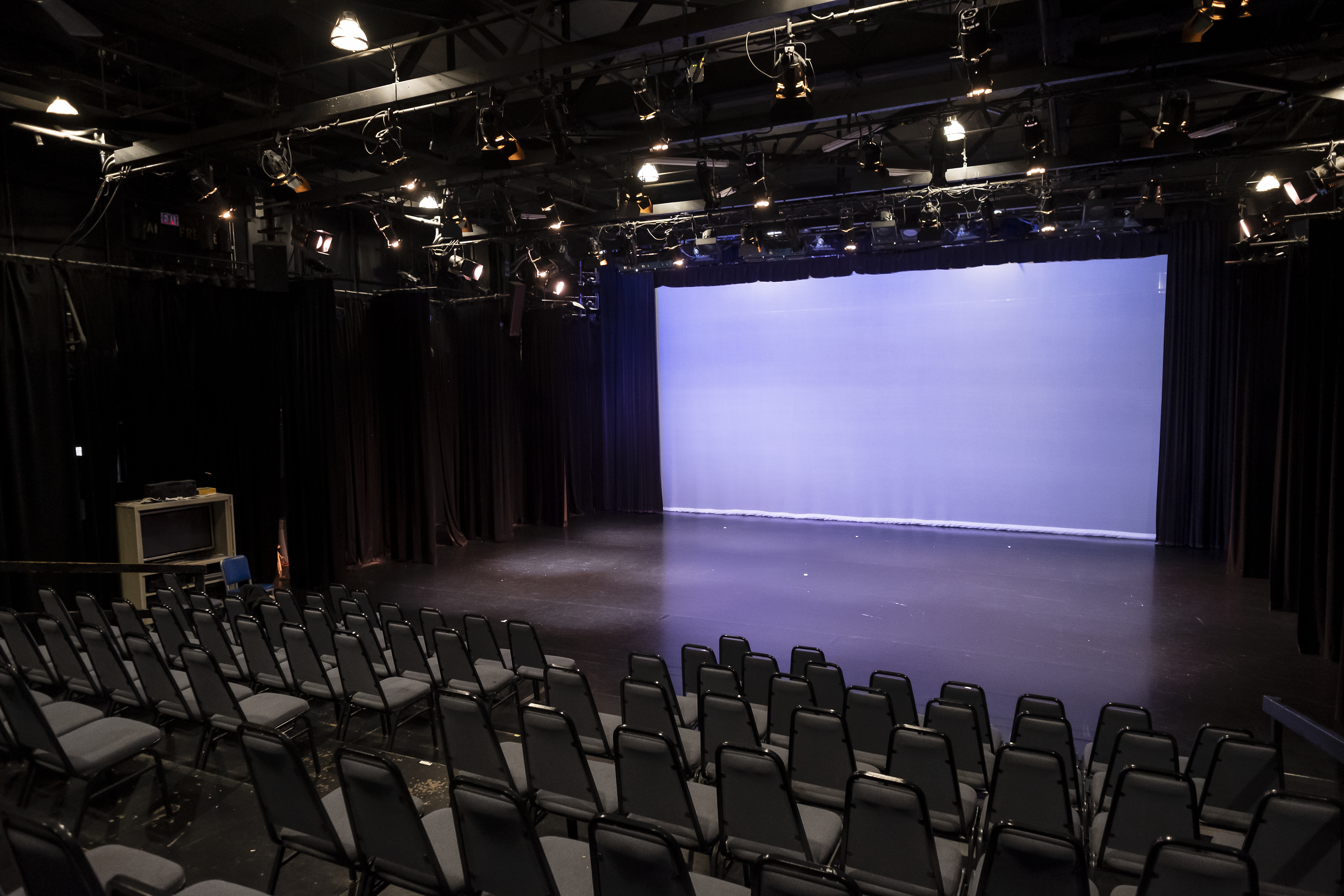 Black box theater with seating and blank screen on stage, lit with purple lights