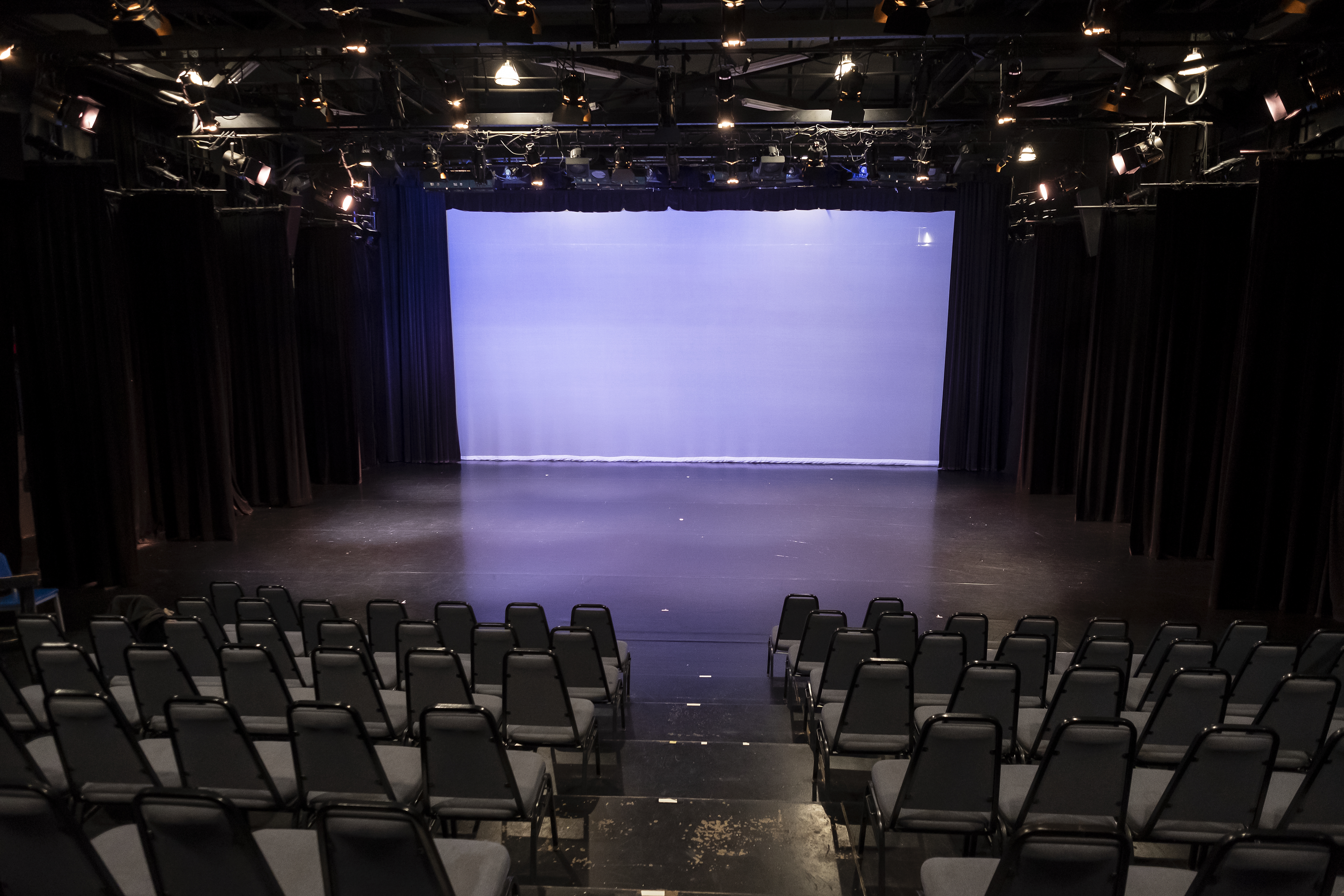 Black box theater with seats on either side of an aisle, leading to empty stage