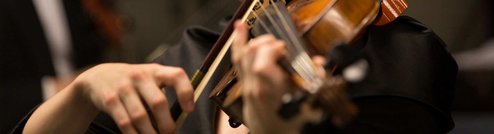 Close up shot of person's hands playing viola