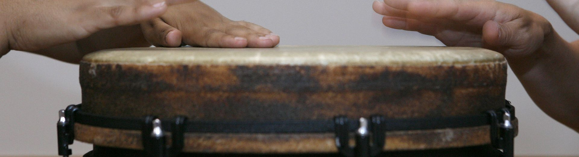 Two sets of hands hitting one drum head