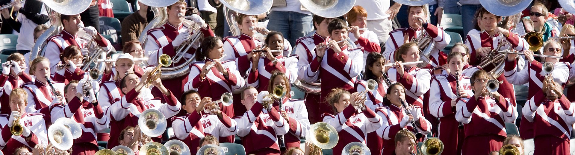 Marching band members playing their instruments, wearing cherry and white uniforms