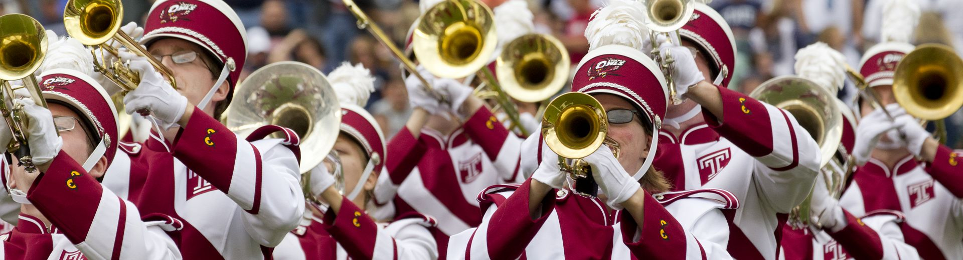 Marching band members playing trombone, wearing cherry and white uniforms
