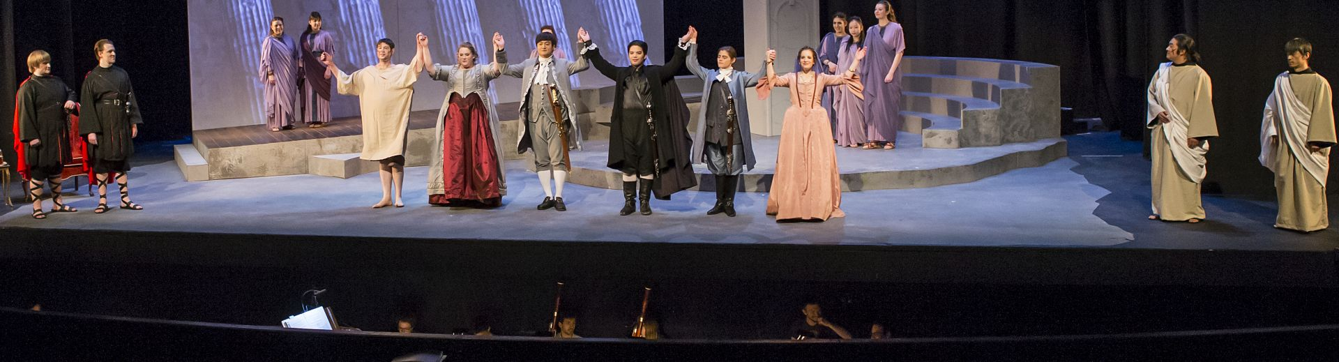 Opera production with players in costume taking a company bow
