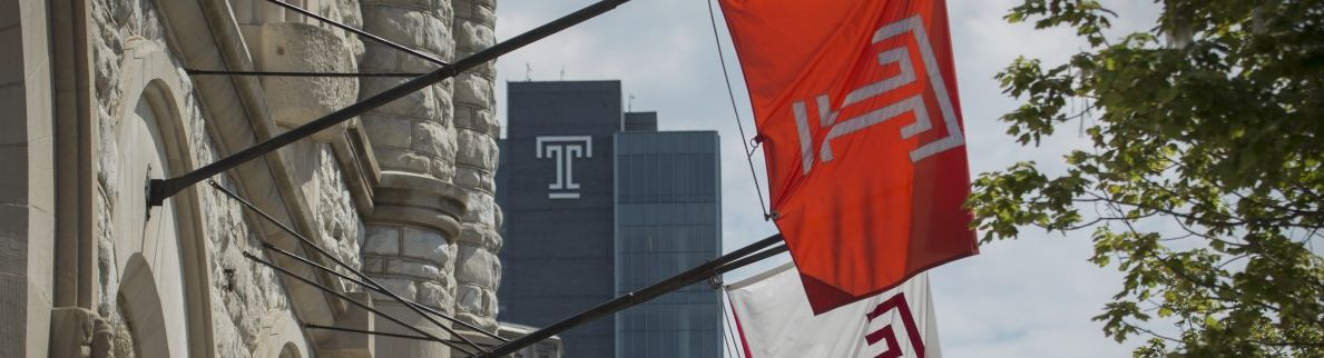 """Two Temple """"T'"""" flags on flag poles coming off of a building"""