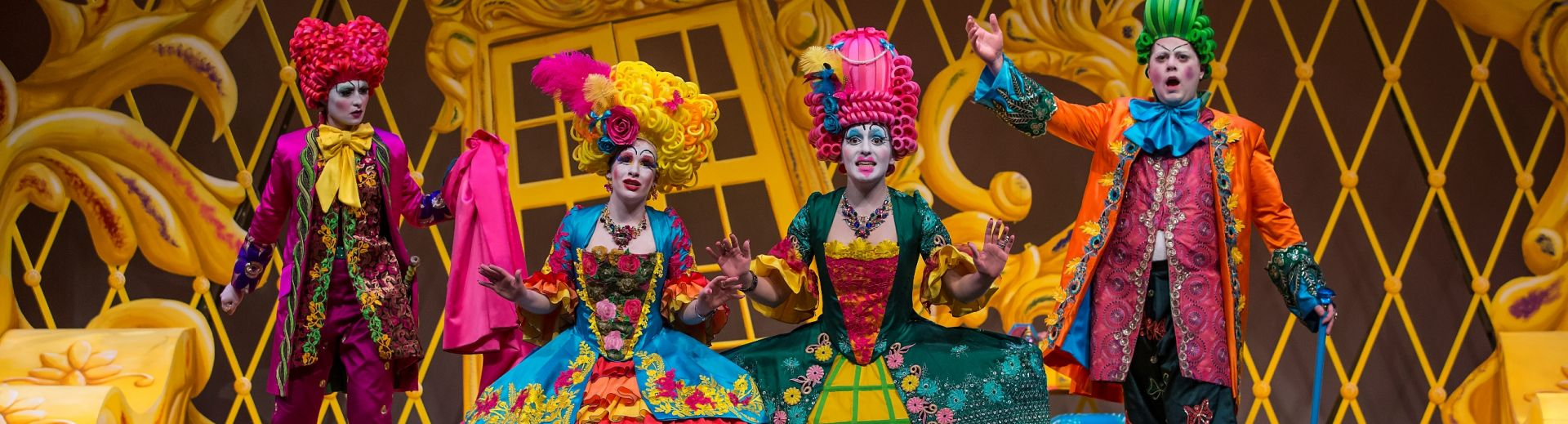 Four vocalists on stage in bright colored costumes and wigs in front of set pieces