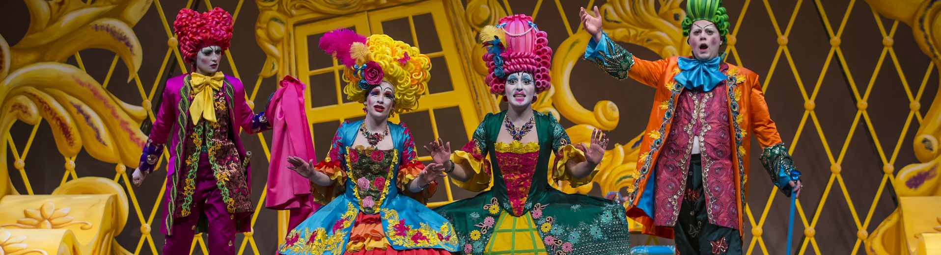 4 singers on stage in color costume in front of an ornate yellow backdrop
