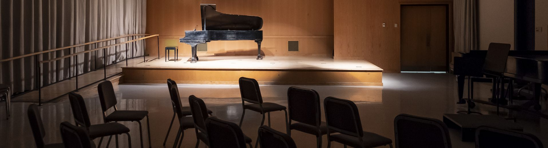 Stage with grand piano on it, audience lights dimmed and spotlight on piano