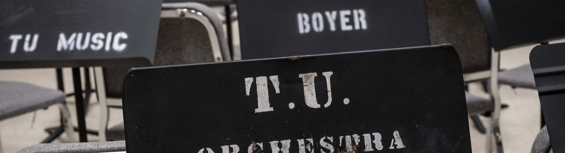 """Metal music stands stamped with the words """"TU Orchestra"""" """"Boyer"""" and """"TU Music"""""""