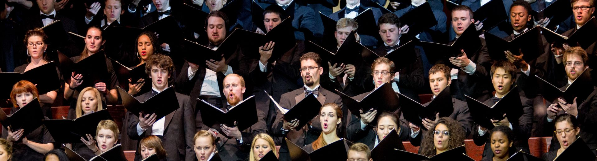 Large choir in concert dress, singing with music folders