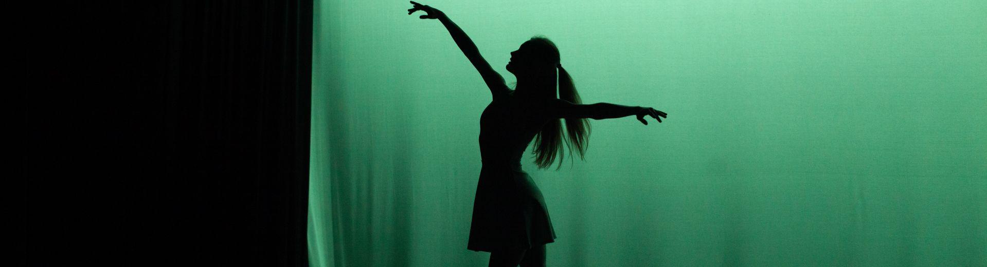 Full-body silhouette of ballet dancer, backlit on stage