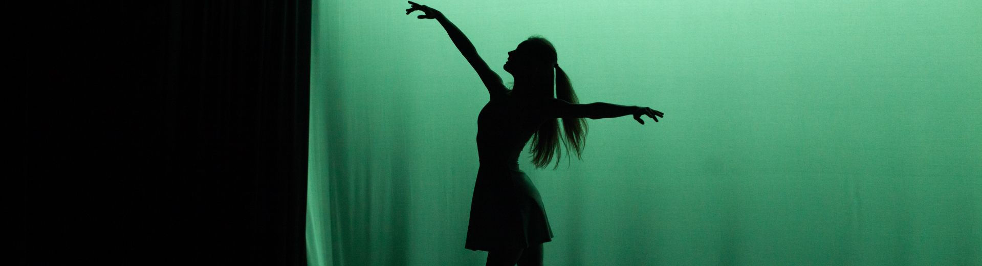 Full-body silhouette of ballet dancer, backlit on stage