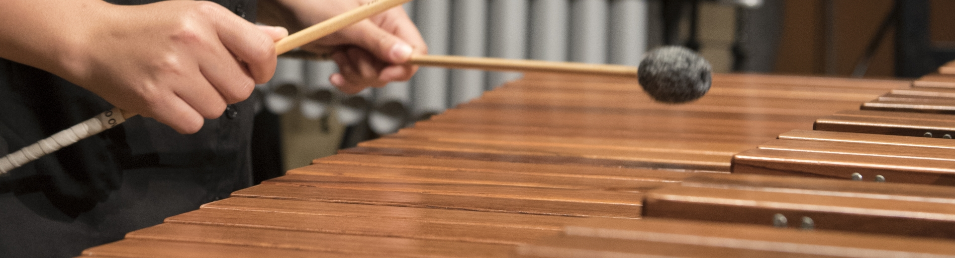 Close up photo of student's hands with soft mallets hitting marimba keys.