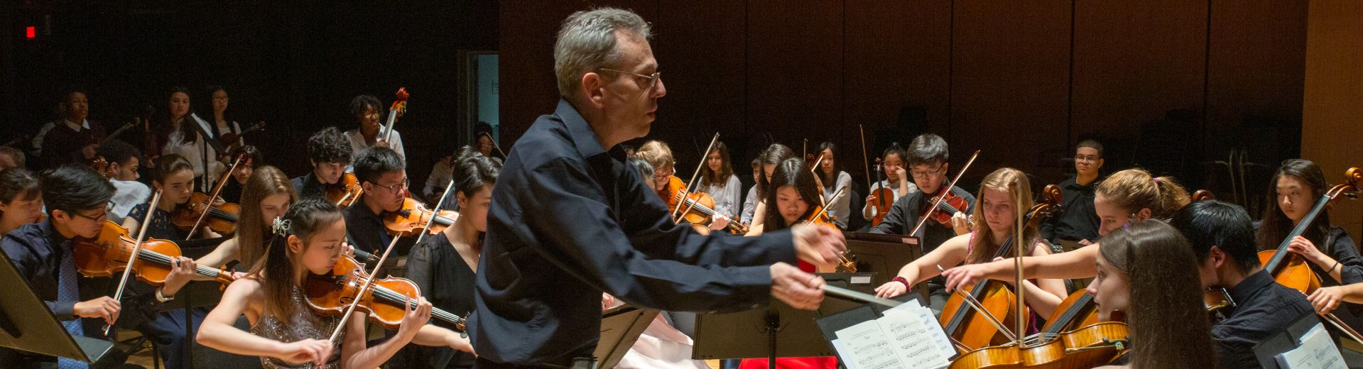 Conductor leading string orchestra at the Temple Performing Arts Center