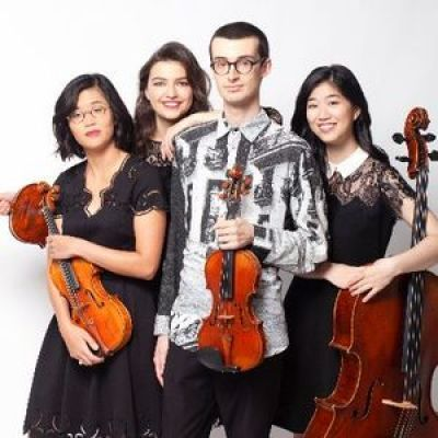 four people dressed in black and white holding string instruments