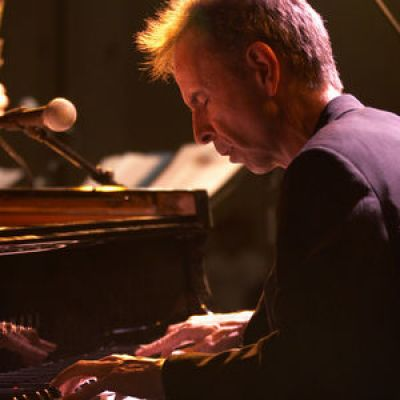 man playing piano with his eyes closed, lit by stage lighting