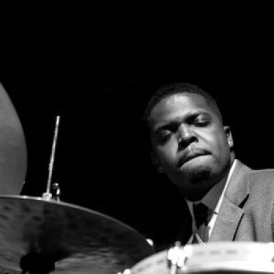 black and white photo of man playing a drum set