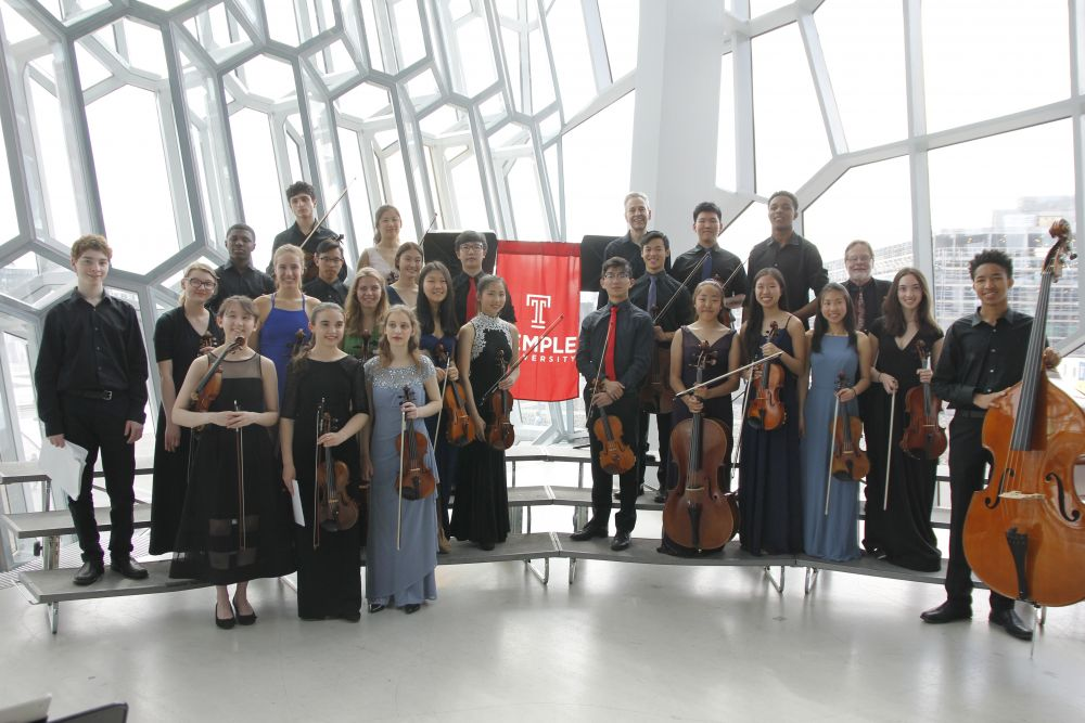 Group shot of students with string instruments standing on risers