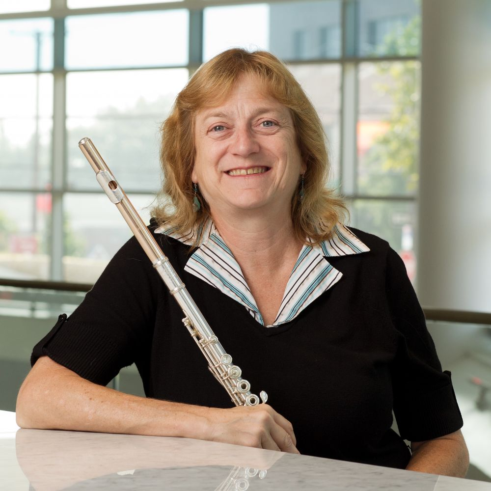 Headshot of blonde woman smiling and holding a flute