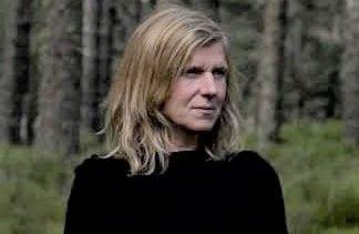 Headshot of a blonde woman in a forest, gazing sideways