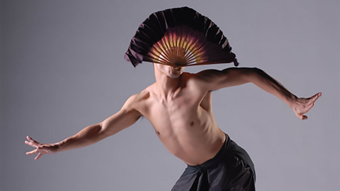 Male dancer with fan on gray background