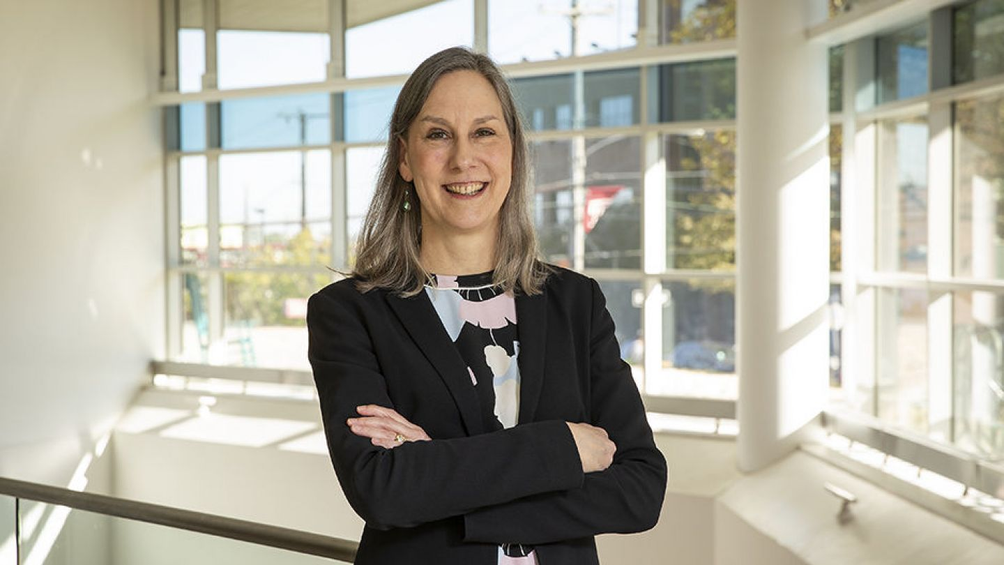 Portrait photo of Dr. Alison Reynolds in front of floor to ceiling windows