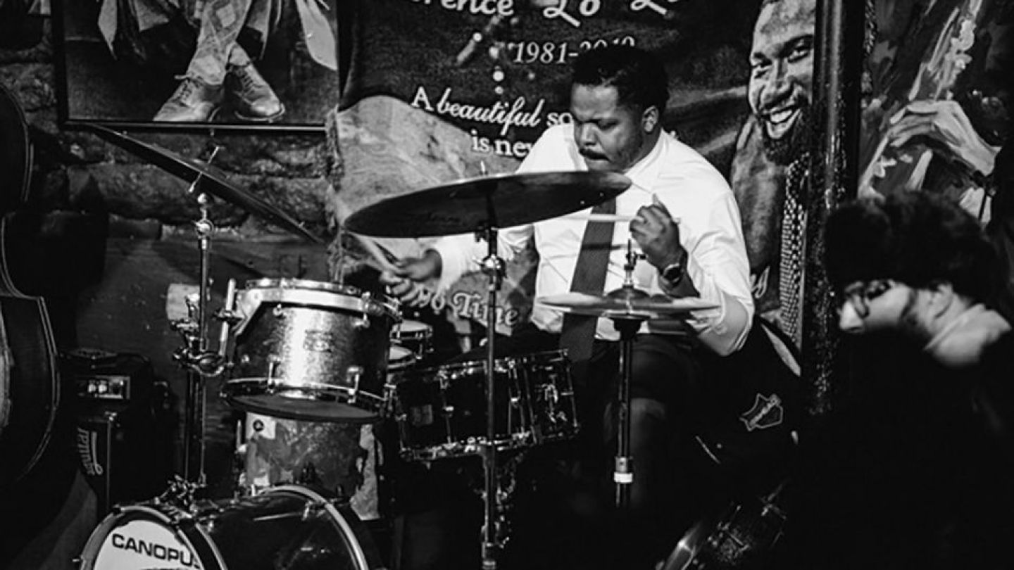 Black and white image of Justin Faulkner at a drum set